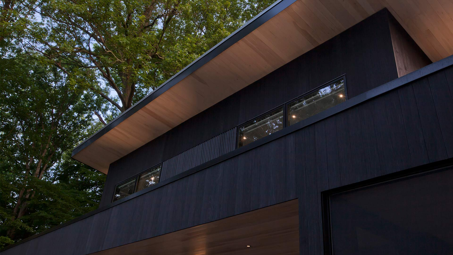 Eastern White Pine Soffit contrasts with Shou Sugi Ban Charred Wood Black Siding and black corrugated metal - Lakeside Modern Cottage (H-LODGE) - Unionville, Indiana, Lake Lemon