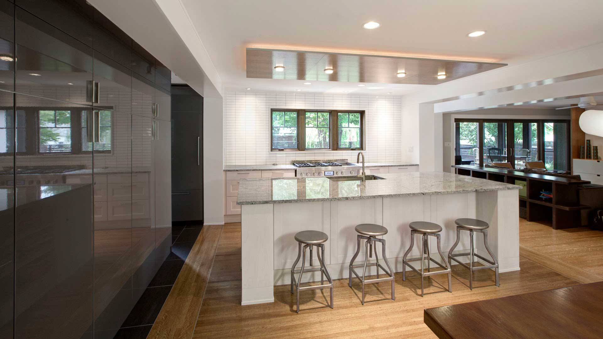 New opened-up kitchen features white and gray IKEA cabinets artfully integrated into the overall architectural solution. Oak ceiling cloud floats over island and incorporates perimeter lighting - Butler Tarkington Modern Tudor - Indianapolis, IN