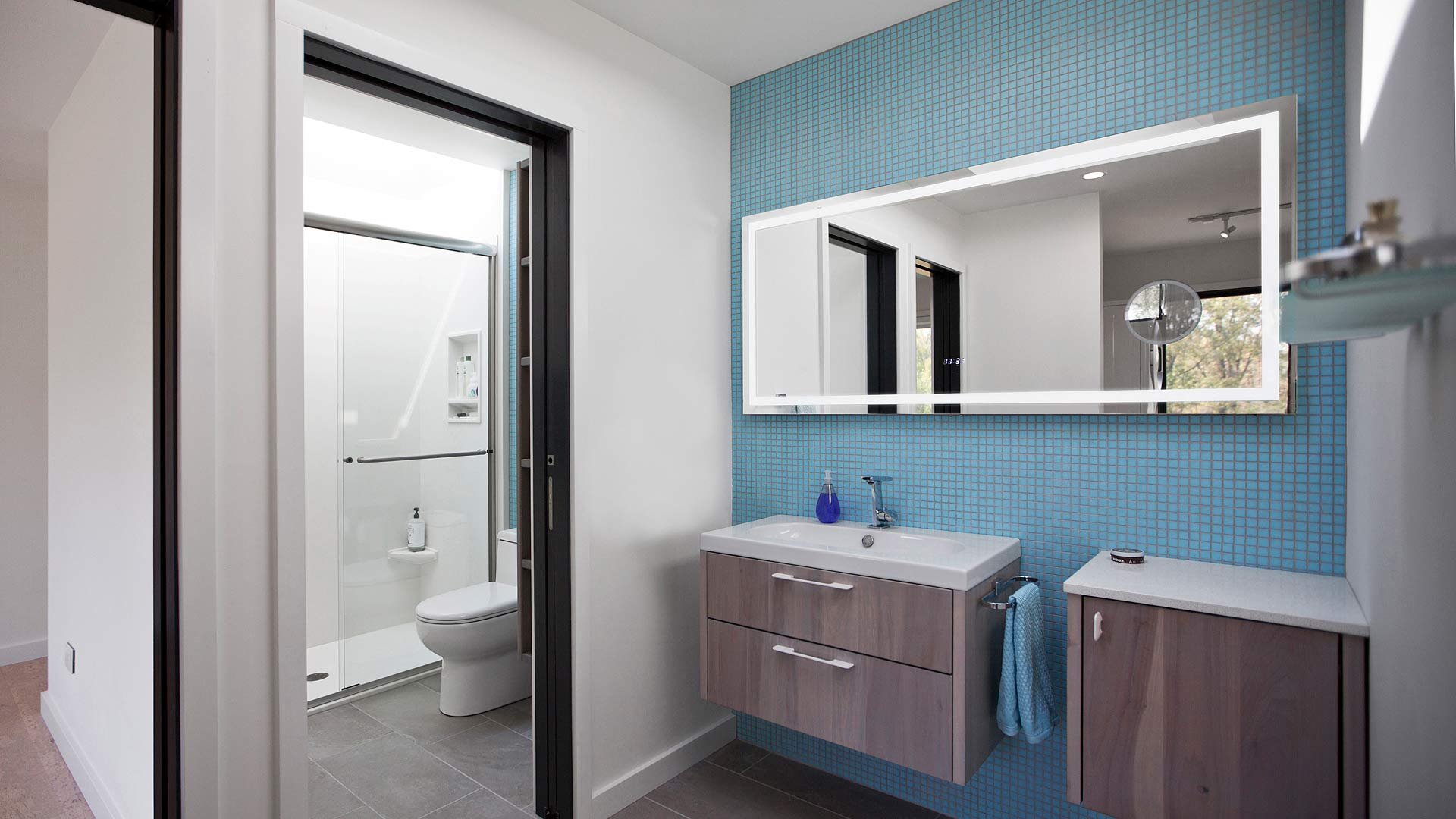 Shared childrens' area bathroom features skylit shower and vanity area with integrally lighted mirror and wall-hung cabinetry - New Modern House 1 (Copperwood) - Zionsville, IN