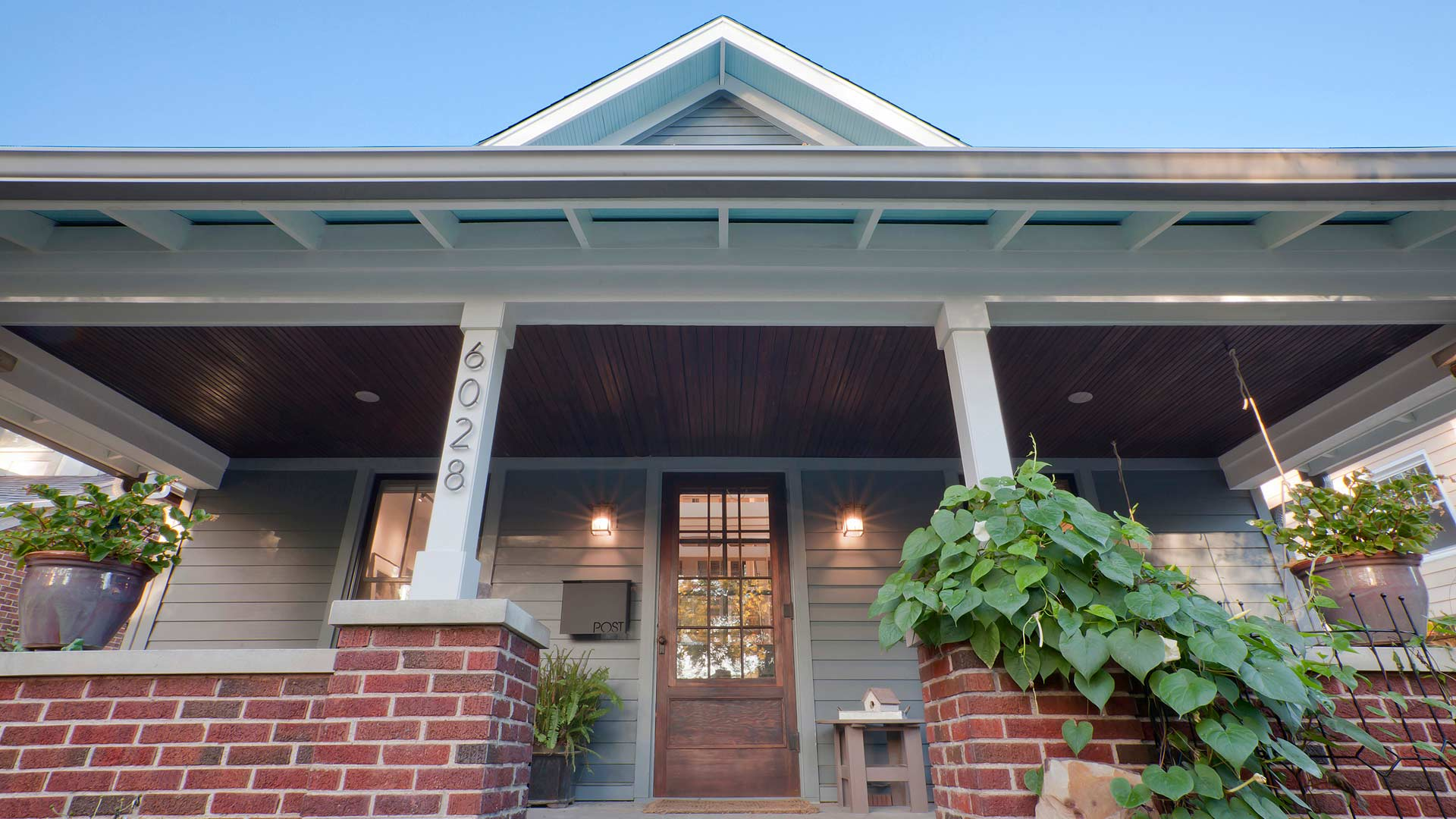 Intimate view of the Craftsman front porch features modern address numerals, original stained beadboard front porch ceiling, modern wall-mounted mailbox, and newly-crafted white-painted exposed rafter tail detailing with light blue-painted eave ceilings in this newly reconstructed Broad Ripple Modern Craftsman Dwelling on Carrollton Avenue - Indianapolis, Indiana