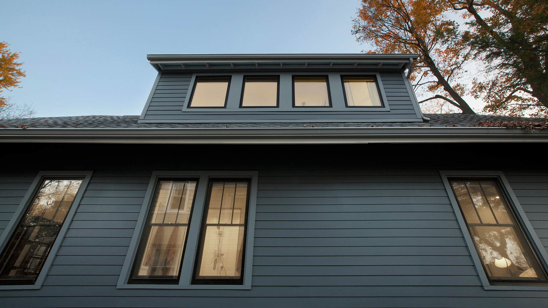 North side view looking up features the shed dormer, fiber-cement lap siding and trims with medium-gray exterior paint and exposed rafter tail Craftsman detailing in this newly reconstructed Broad Ripple Modern Craftsman Dwelling on Carrollton Avenue - Indianapolis, Indiana