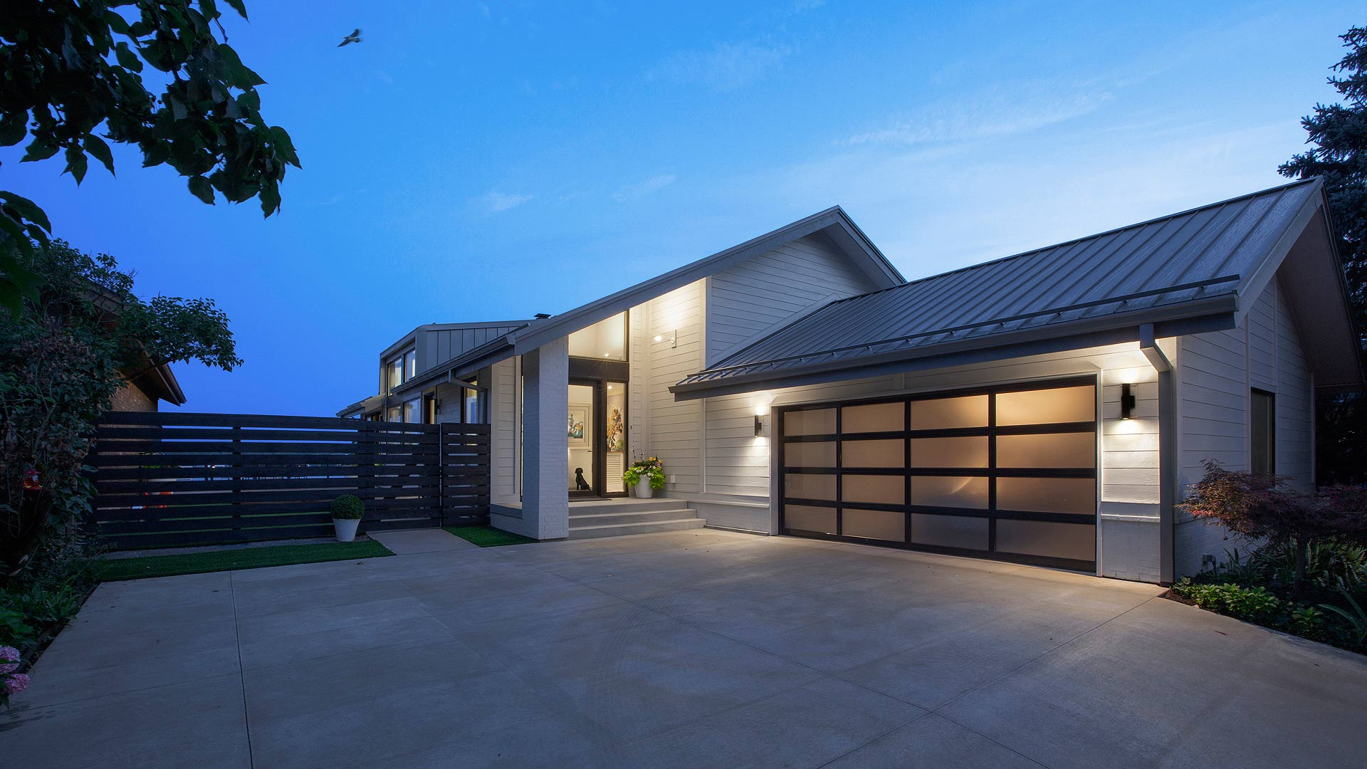 New renovation reinterprets 1980's cottage into new modern dwelling fitting in with neighborhood covenants, including new entry gallery, siding, glass overhead door, and standing seam metal roof - Modern Lakehouse Renovation - Clearwater