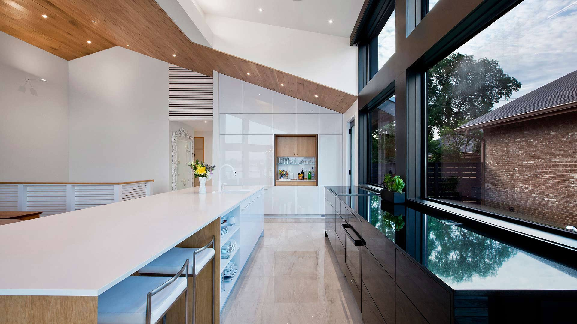 New kitchen is highlighted by the giant south facing dormer, hidden beverage counter, giant 14-foot island, and vaulted white oak ceiling - Modern Lakehouse Renovation - Clearwater