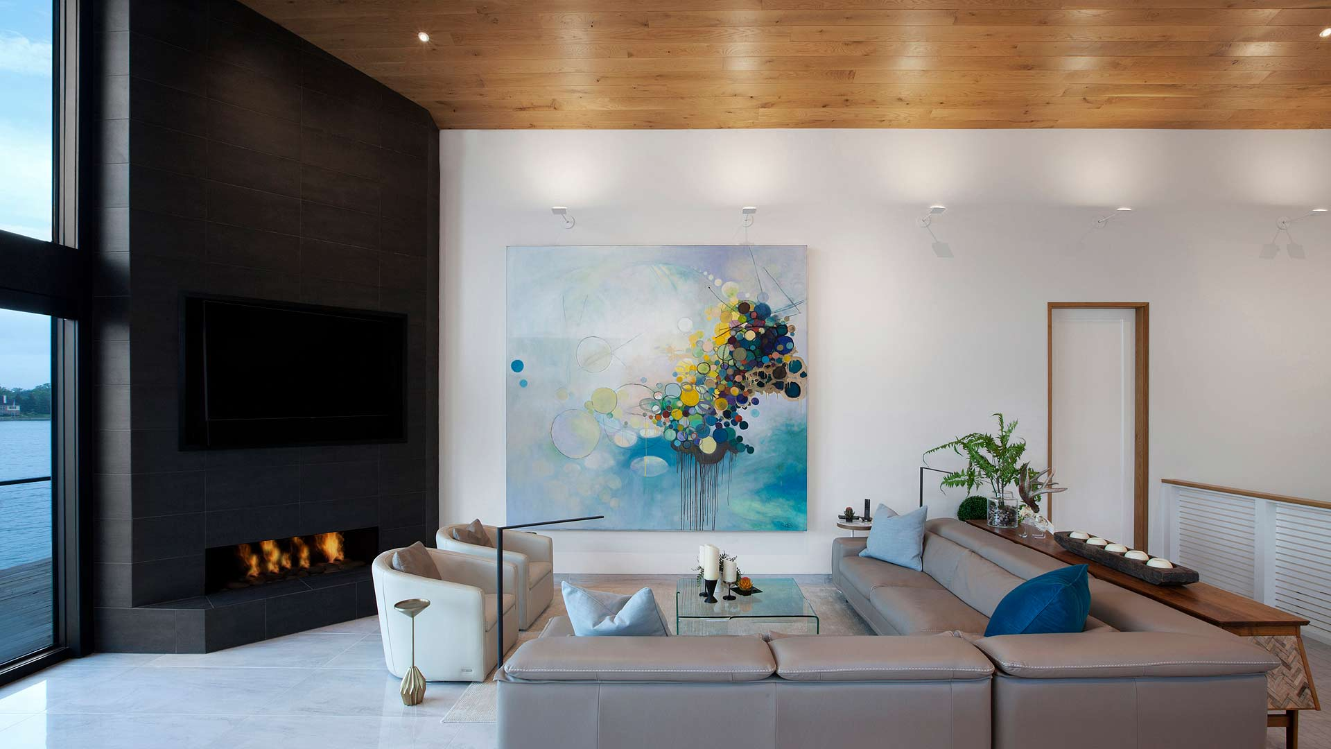 Living space re-clads existing fireplace adds new white oak vaulted ceiling with uplighting and large custom art within new open concept plan - Modern Lakehouse Renovation - Clearwater