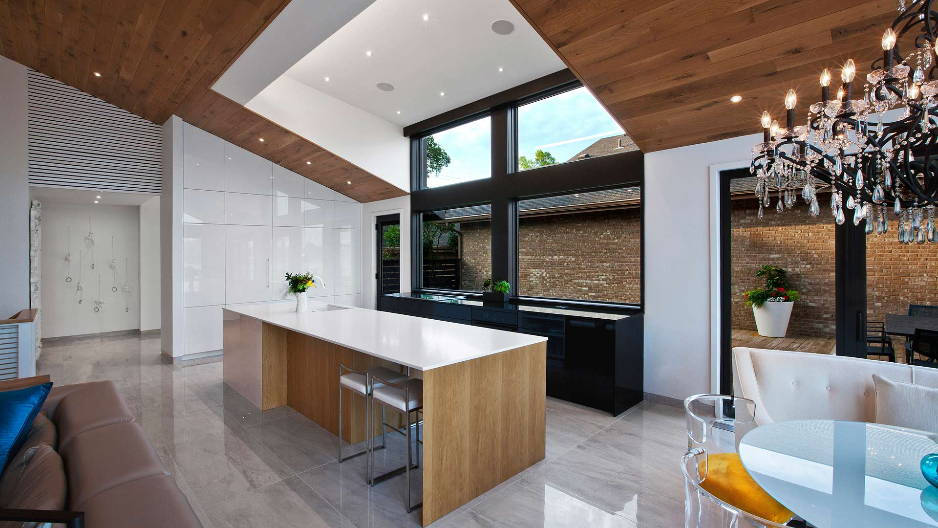 New kitchen is highlighted by the oversized south facing dormer, giant 14-foot island, black back counter, glass chandelier, and vaulted white oak ceiling - Modern Lakehouse Renovation - Clearwater