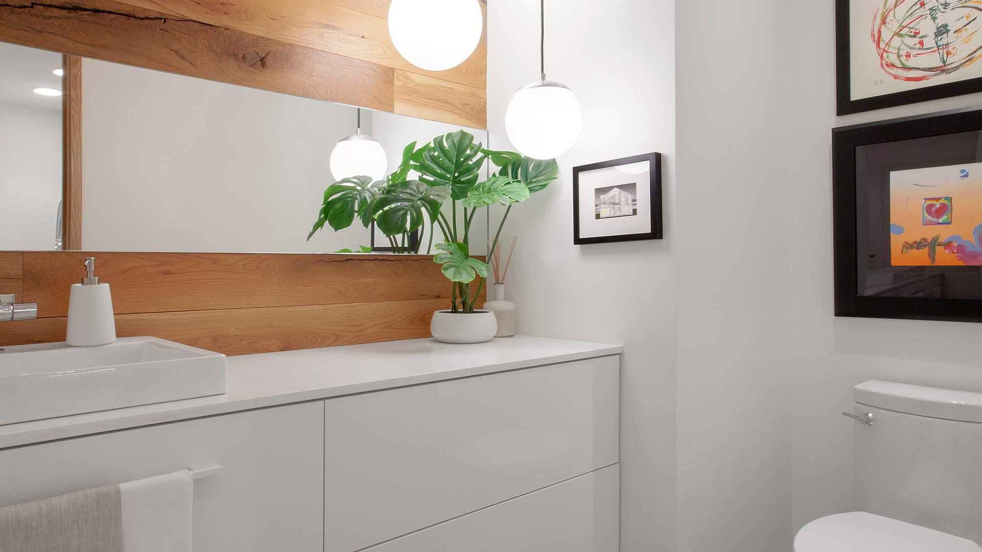 New powder room incorporates white oak into vanity wall with floating white vanity, horizontal mirror, and ball pendant lighting - as always, client adds nice personal touches including plants and artwork - Modern Lakehouse Renovation - Clearwater