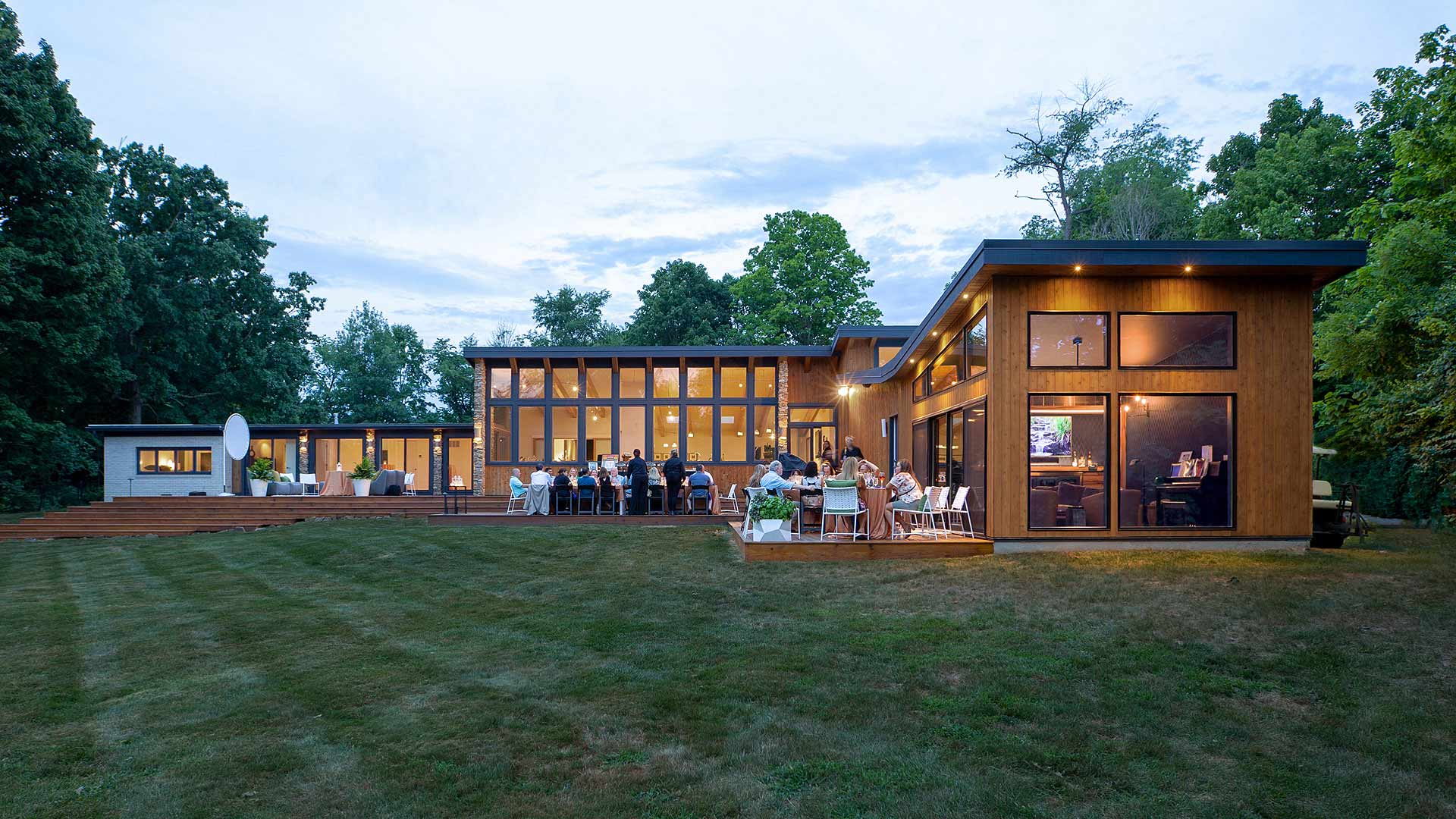 Rear Exterior Elevation During Summer Party - Cigar Room Addition - Shed Roofs - Cedar Siding - Midcentury Modern Addition (Cigar Room) - Brendonwood, Indianapolis