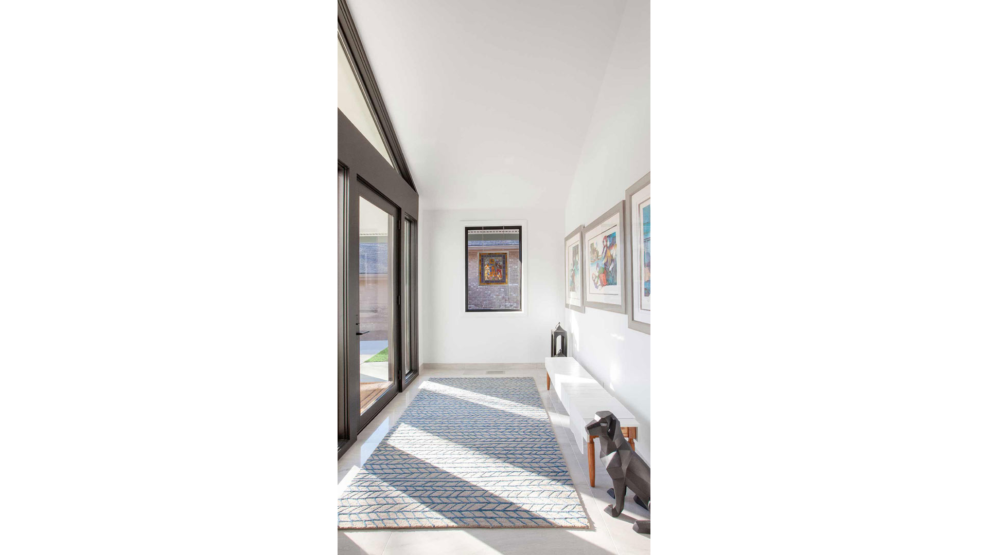 Entry Foyer includes large sidelights and transom windows, custom bench, colorful artwork, and stained glass - Modern Lakehouse Renovation - Clearwater - Indianapolis