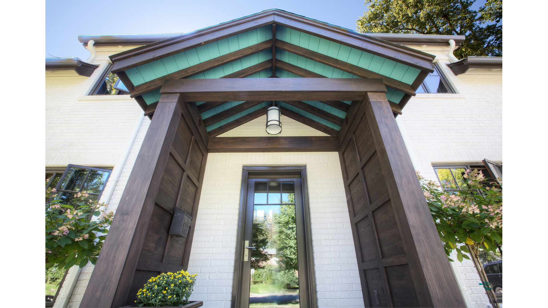 Front Exterior Elevation features new gable entry porch with Tudor/Craftsman details including exposed rafters and Robin's egg blue soffit color - Butler Tarkington Modern Tudor - Indianapolis, IN