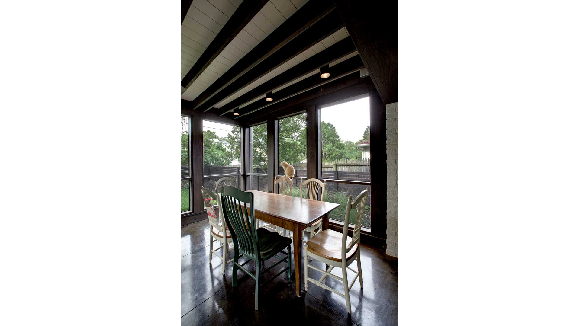 Screened porch exposes structure and roof decking above to continue the Tudor style. Stained concrete floor slopes outward with drainage detail at bottoms of wall. - Butler Tarkington Modern Tudor - Indianapolis, IN