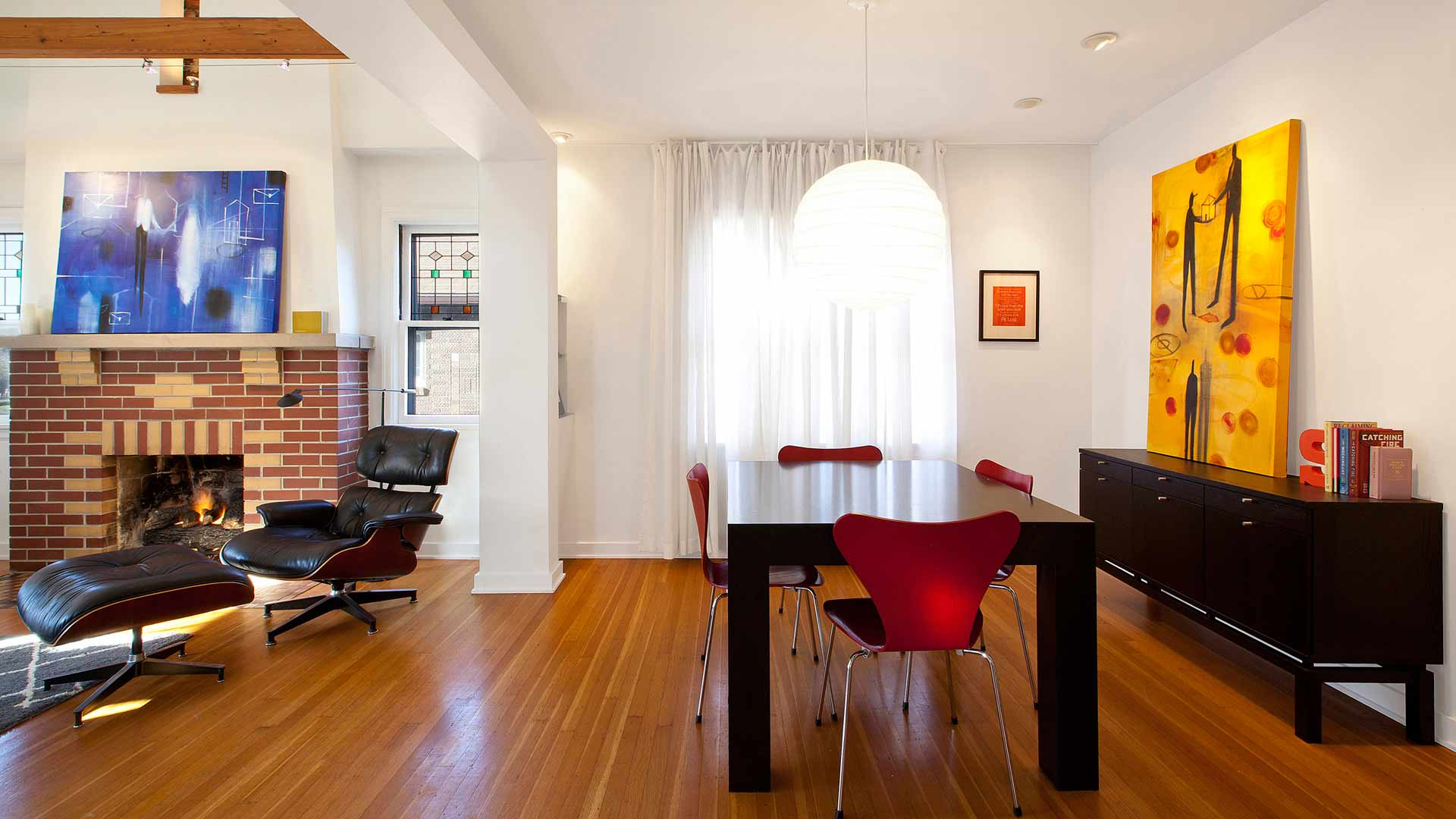 Dining Room includes commissioned artwork, custom dining table, Eames Lounge, and Arne Jacobsen 7 Chairs in red - Classic Irvington Tudor Remodel - Indianapolis, IN