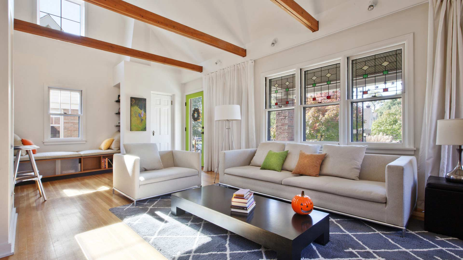 Renovated Living space adds vaulted ceiling with exposed beams, art niche, window seat and new modern details - Classic Irvington Tudor Remodel - Indianapolis, IN