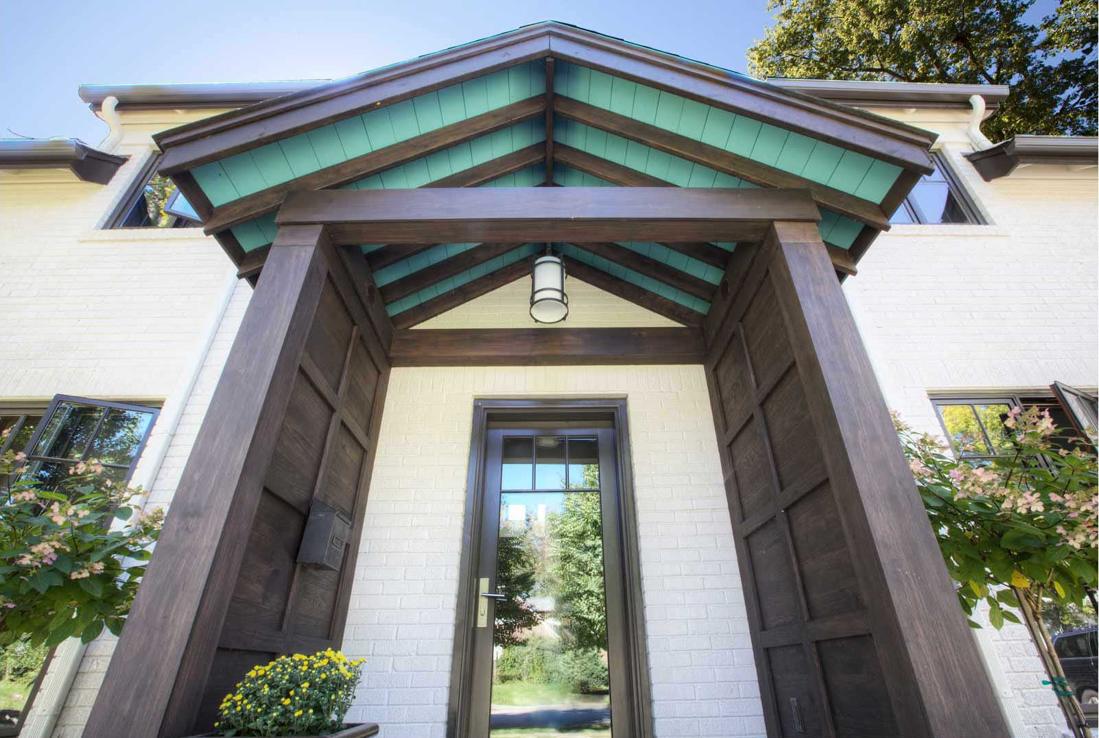 New entry porch reinforces Craftsman-Tudor character of existing house while hinting of a revitalized interior - Butler-Tarkington Modern Tudor - Indianapolis, IN