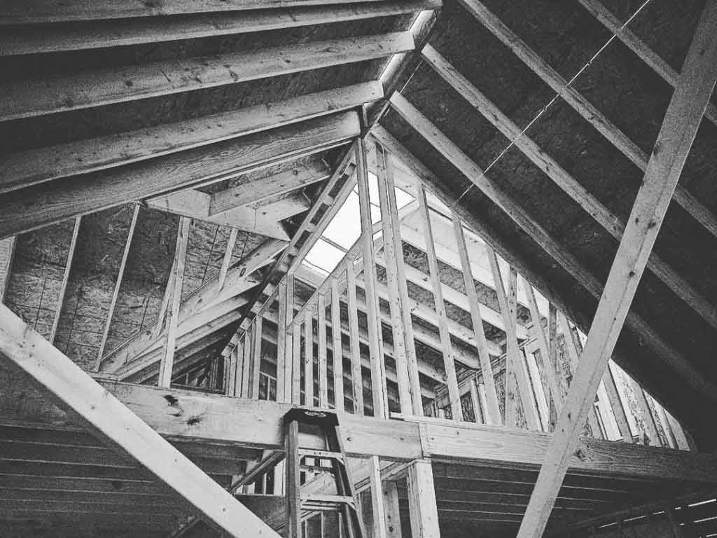Broad Ripple Craftsman Renovation – Nearing framing completion, you can get a glimpse at the skylight from the newly vaulted living room - Modern Craftsman Renovation - Indianapolis, IN
