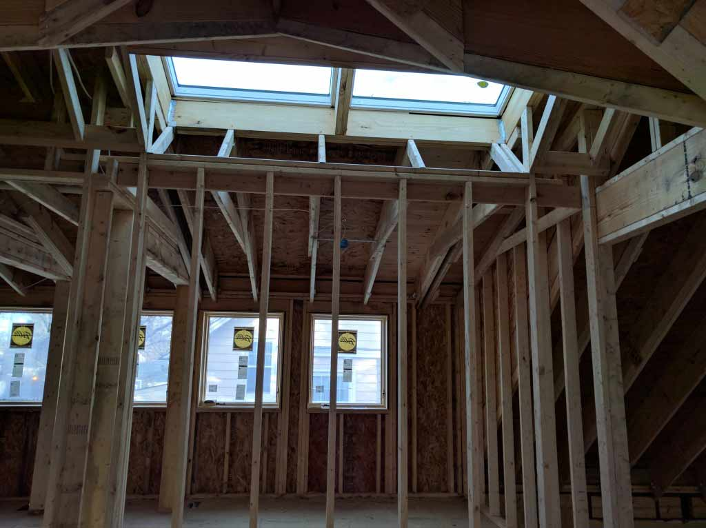 Broad Ripple Craftsman Renovation – the north-facing skylight at the stair provide an even lighting level. Without any finishes installed the skylight is doing a great job at washing the framing lumber with daylight - Modern Craftsman Renovation - Indianapolis, IN