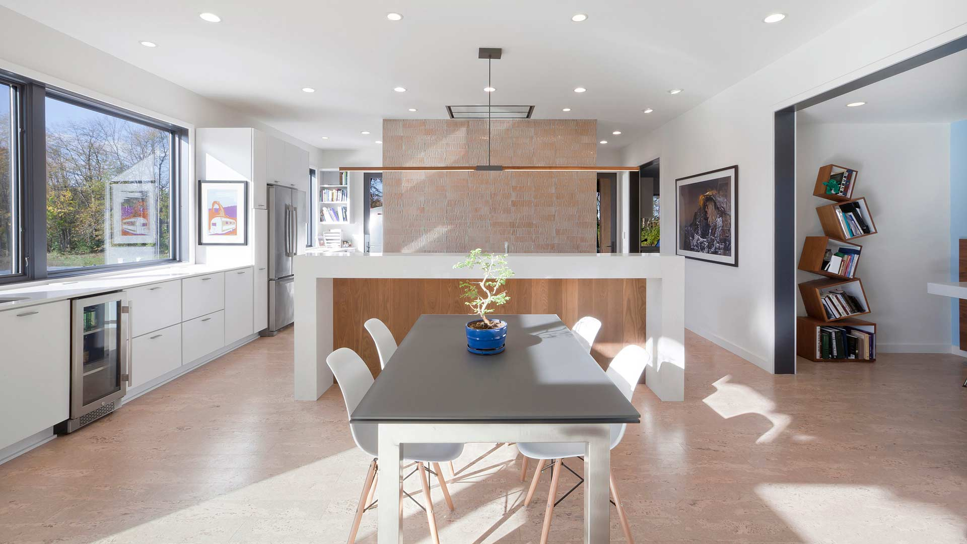 Open concept Dining and Kitchen features thermally treated wood on island, cork flooring, and expansive window views - New Modern House 1 (Copperwood) - Zionsville, IN