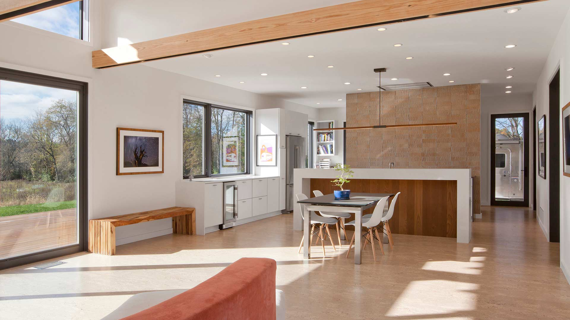 View from open concept living room to dining and kitchen areas - cork flooring, exposed beams, vaulted ceiling, clerestory windows, orange tile, thermally treated wood, white slab door cabinets, Airstream - New Modern House 1 (Copperwood) - Zionsville, IN
