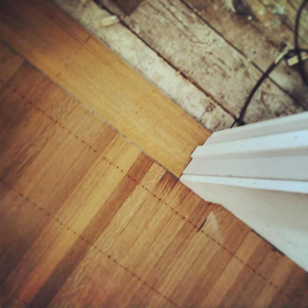 New white oak flooring punctuates interior door openings with tile strip-edged threshold transitions (details) - Butler Tarkington Modern Tudor - Indianapolis, IN