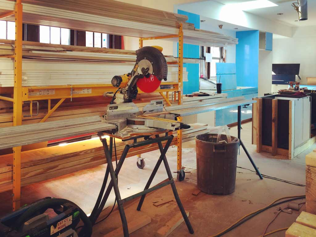 Broad Ripple Craftsman Renovation – Trim carpentry is underway. The trim materials have been acclimating to the interior space. Note the cabinetry in place with the protective blue film - Modern Craftsman Renovation - Indianapolis, IN