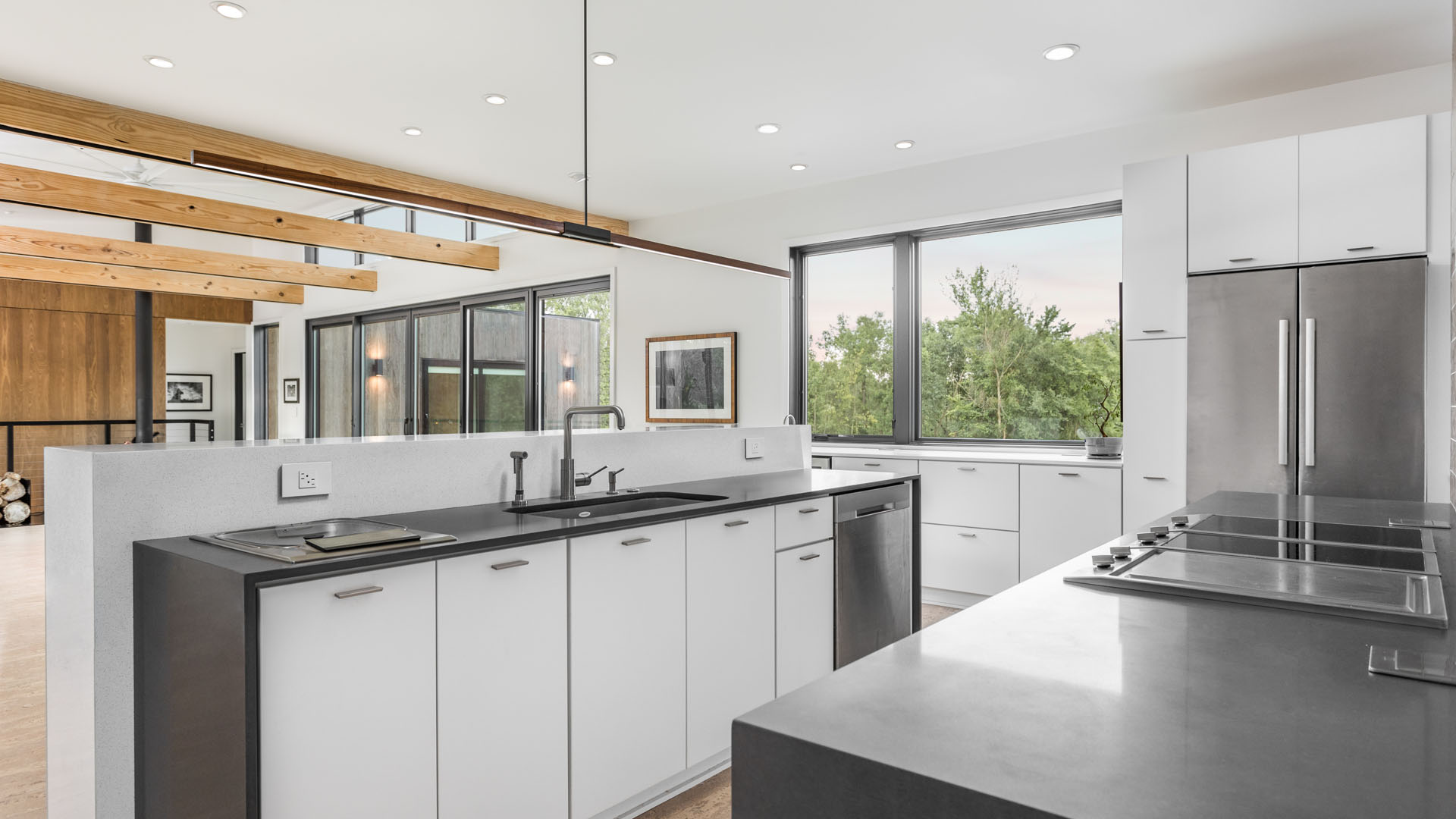 View of kitchen, dining, living room with vaulted ceilings and clerestory windows - stainless steel appliances and white flat door kitchen cabinets and exposed beams - New Modern House 1 (Copperwood) - Zionsville, IN