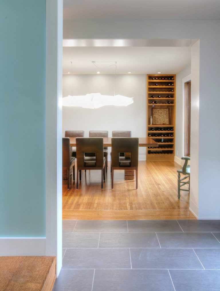 Main entry features new tile flooring and views to original living room in foreground and new enhanced dining room beyond. Modern dining room pendant light fixture and custom oak wine shelves highlight the dining room - Butler Tarkington Modern Tudor - Indianapolis, IN