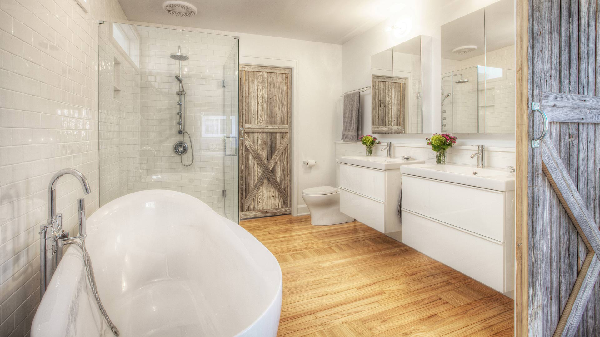 Master Bedroom opens directly to Master Spa via new custom barn doors. Wall hung vanities and freestanding tub coexist nicely with shower, while clerestory window borrows light from skylit middle hallway - Broad Ripple Bungalow Phase 1 - Indianapolis, IN