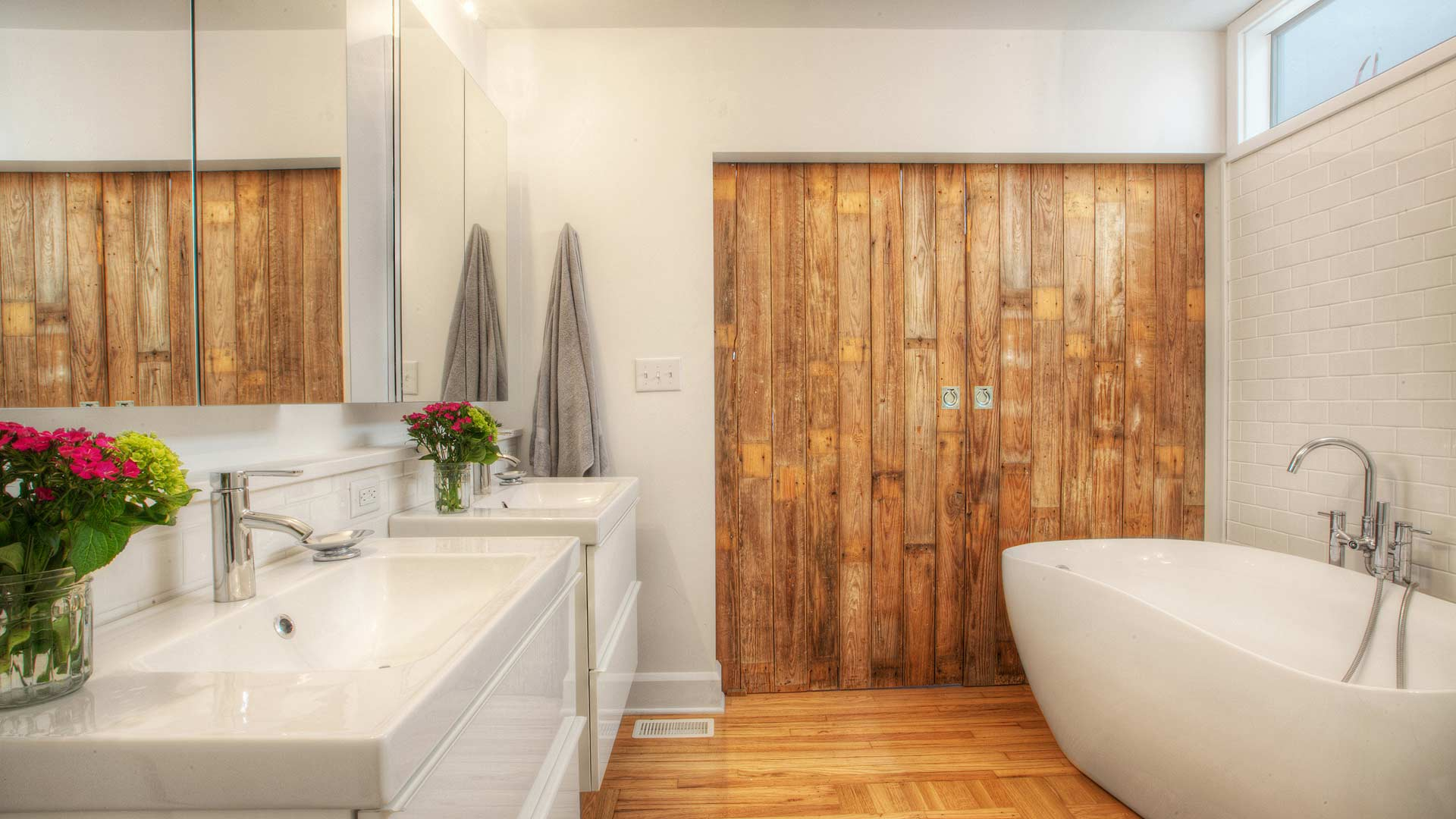 Master Bathroom opens directly to Master Bedroom via new custom barn doors. Wall hung vanities and freestanding tub coexist nicely, while clerestory window borrows light from skylit middle hallway - Broad Ripple Bungalow Phase 1 - Indianapolis, IN