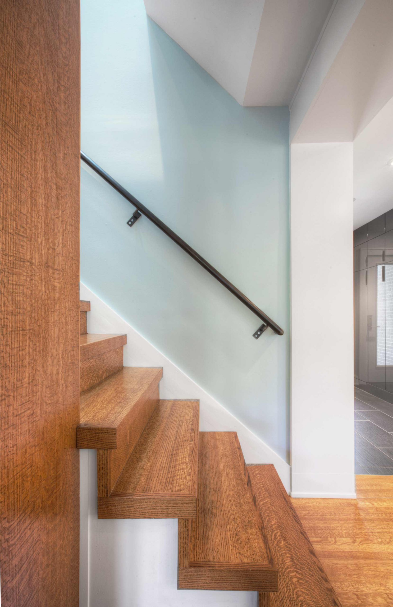 New back stair leads directly from Family Room/Kitchen area to Bedroom Suites upstairs. Oak details integrate with built-in shelves above and below - Butler Tarkington Modern Tudor - Indianapolis, IN