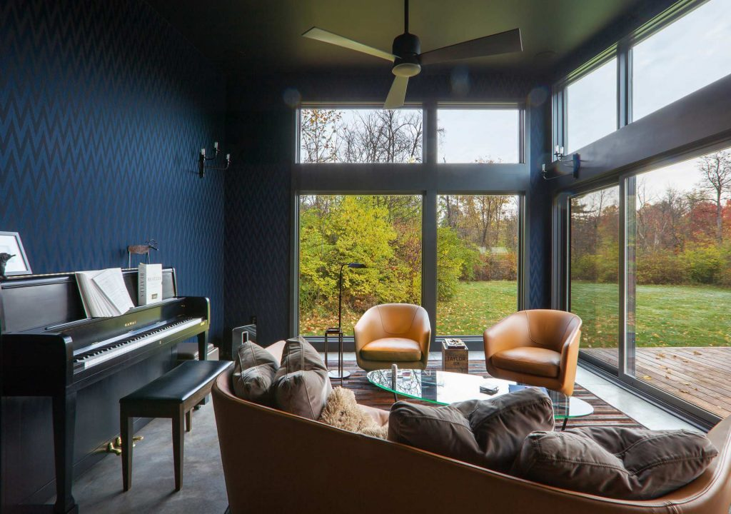 Cigar Room Interior maximizes views of backyard on fall afternoon - upright piano, orange leather chairs, black ceiling fan, polished concrete floors - Midcentury Modern Addition (Cigar Room) - Brendonwood, Indianapolis