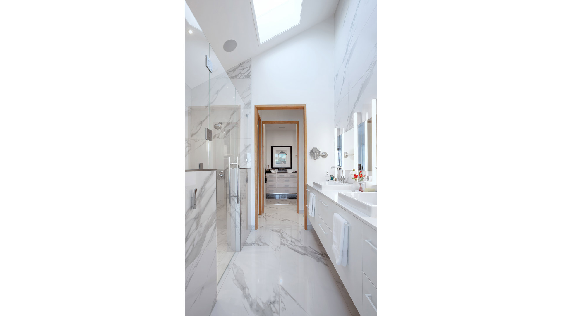 Master Spa Bathroom features porcelain floor + wall tile, skylight, vaulted ceilings, white floating vanity, frameless glass shower enclosure, half-height shower walls, and white oak casings - Modern Lakehouse Renovation - Clearwater - Indianapolis