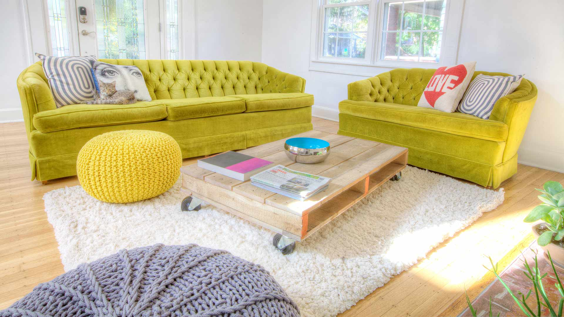 Knitted Poufs Rule the Nest - Retro green sofas, colorful poufs, and wheeled coffee table highlight living space - Broad Ripple Bungalow Phase 1 - Indianapolis, IN