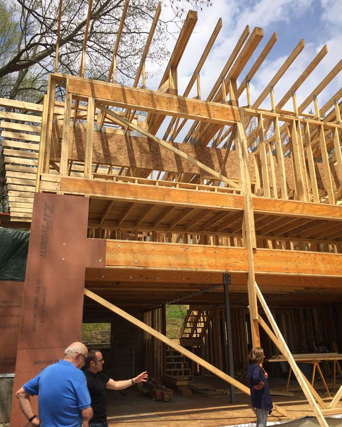 Derek Mills walks Client (Don and JoAnn) through the project during the framing stage. Trusses achieve cantilevers on all sides without the use of steel framing - Lakeside Modern Cottage (H-LODGE) - Unionville, Indiana, Lake Lemon