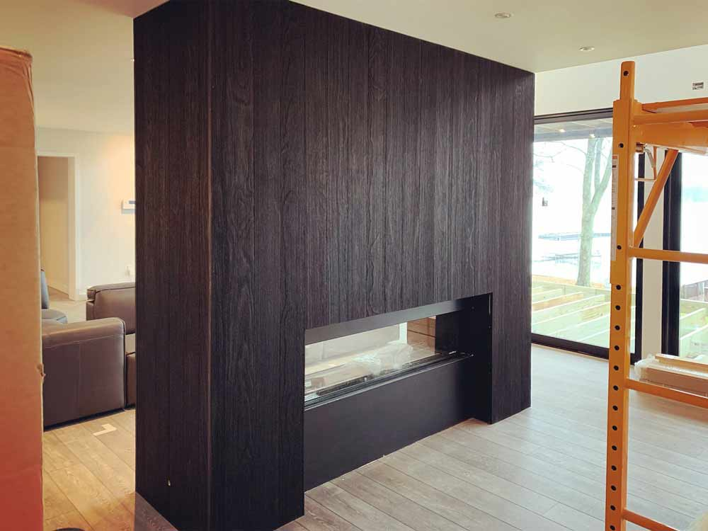 Charred wood cladding wraps two sided gas fireplace (view from kitchen/dining area. Flooring is luxury vinyl tile - Lakeside Modern Cottage (H-LODGE) - Unionville, Indiana, Lake Lemon