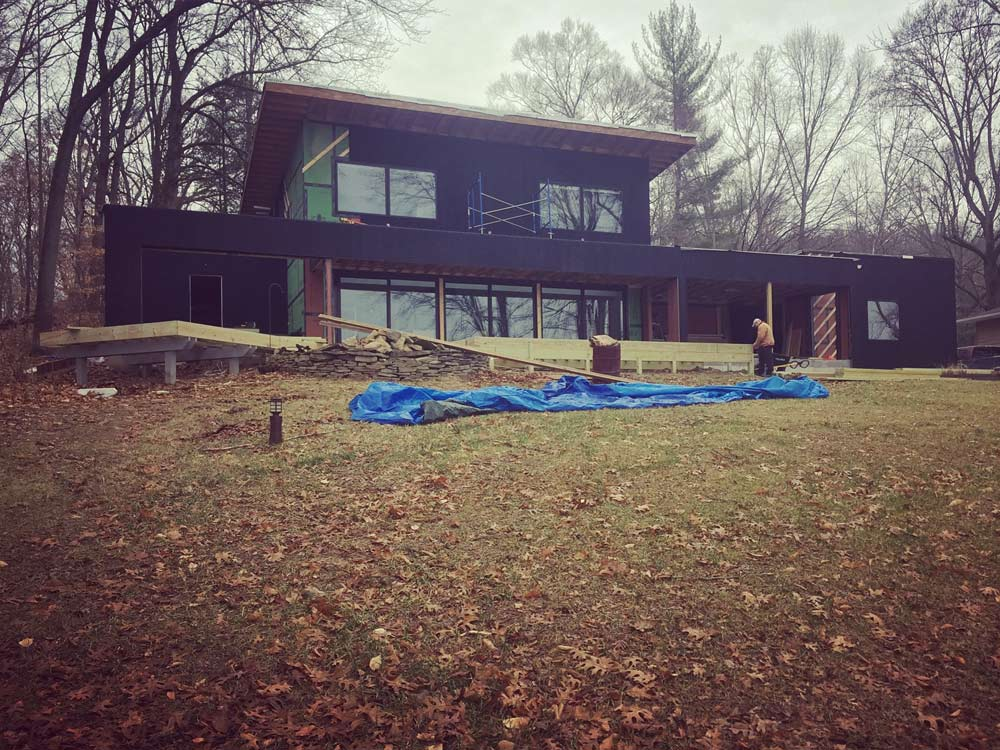 Lakeside View of exterior progress - black wood siding + shed roof + flat roofs (Chris Adams) - Unionville, Indiana, Lake Lemon