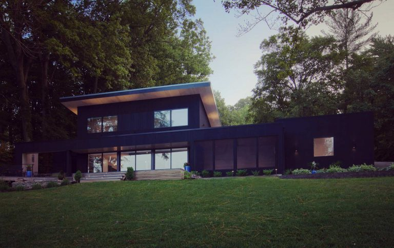 View from lakeside features overhanging shed roof with Eastern White Pine soffits, black charred shou-sugi ban siding, and screened porch between house and garage - Lakeside Modern Cottage (H-LODGE) - Unionville, Indiana, Lake Lemon