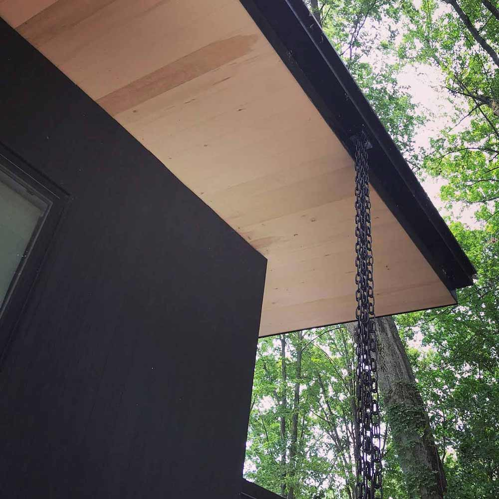 Shed roof drains to box-style gutter and rain-chain detail. Soffits are Eastern White Pine prefinished, and siding is black shou sugi ban - Lakeside Modern Cottage (H-LODGE) - Unionville, Indiana, Lake Lemon