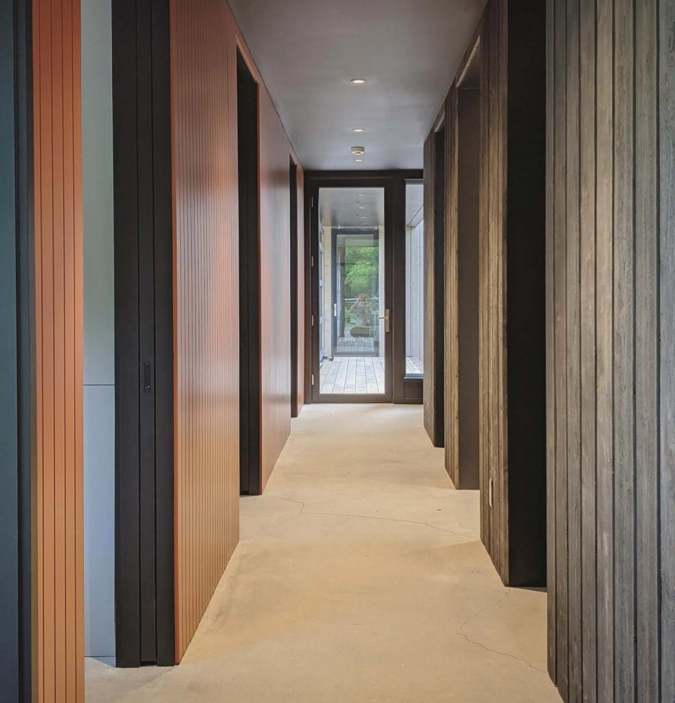 Nearing Completion: Entry hall carries exterior materials to the interior (Cedar + Corten Steel) - Back40House - Pendleton, IN