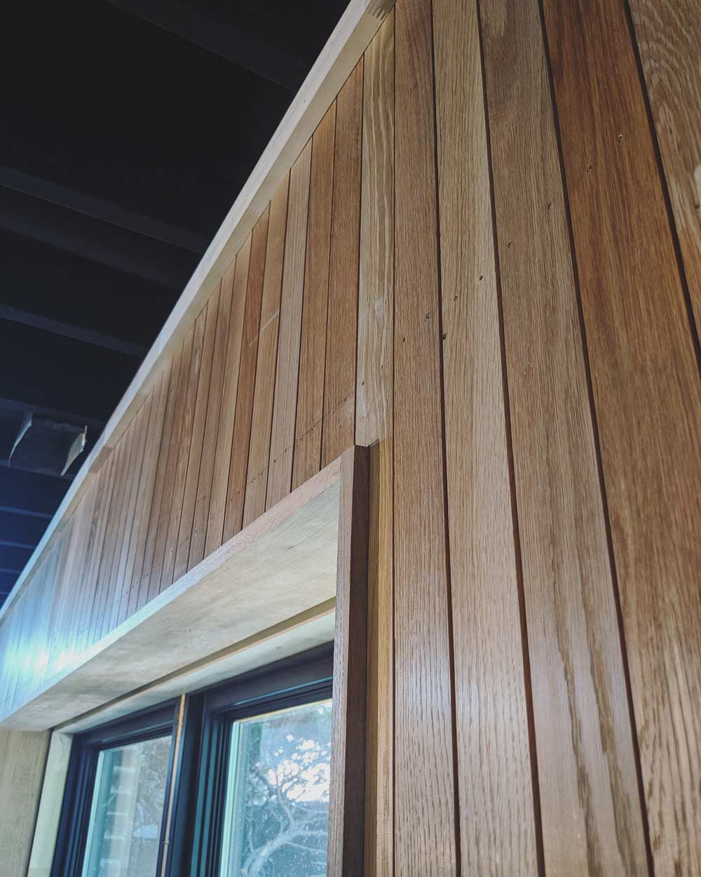 Exterior wall gets a new vertical oak skin + black-clad wiindows. Exposed ceiling structure is painted black - Scandinavian Modern Interior - Indianapolis, IN - Trader's Point