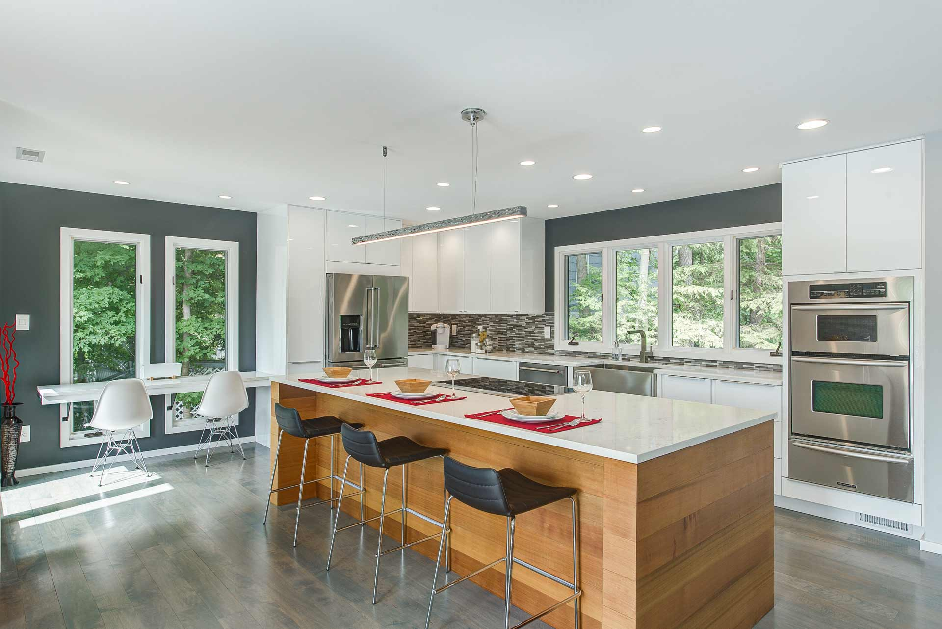 New expanded kitchen space includes new Cedar wrapped island, white quartz tops, and white IKEA cabinetry with gray accent walls and a laptop counter - Reef Court Light Renovation - Geist Reservoir - Indianapolis, IN - Photo by Structured Photography