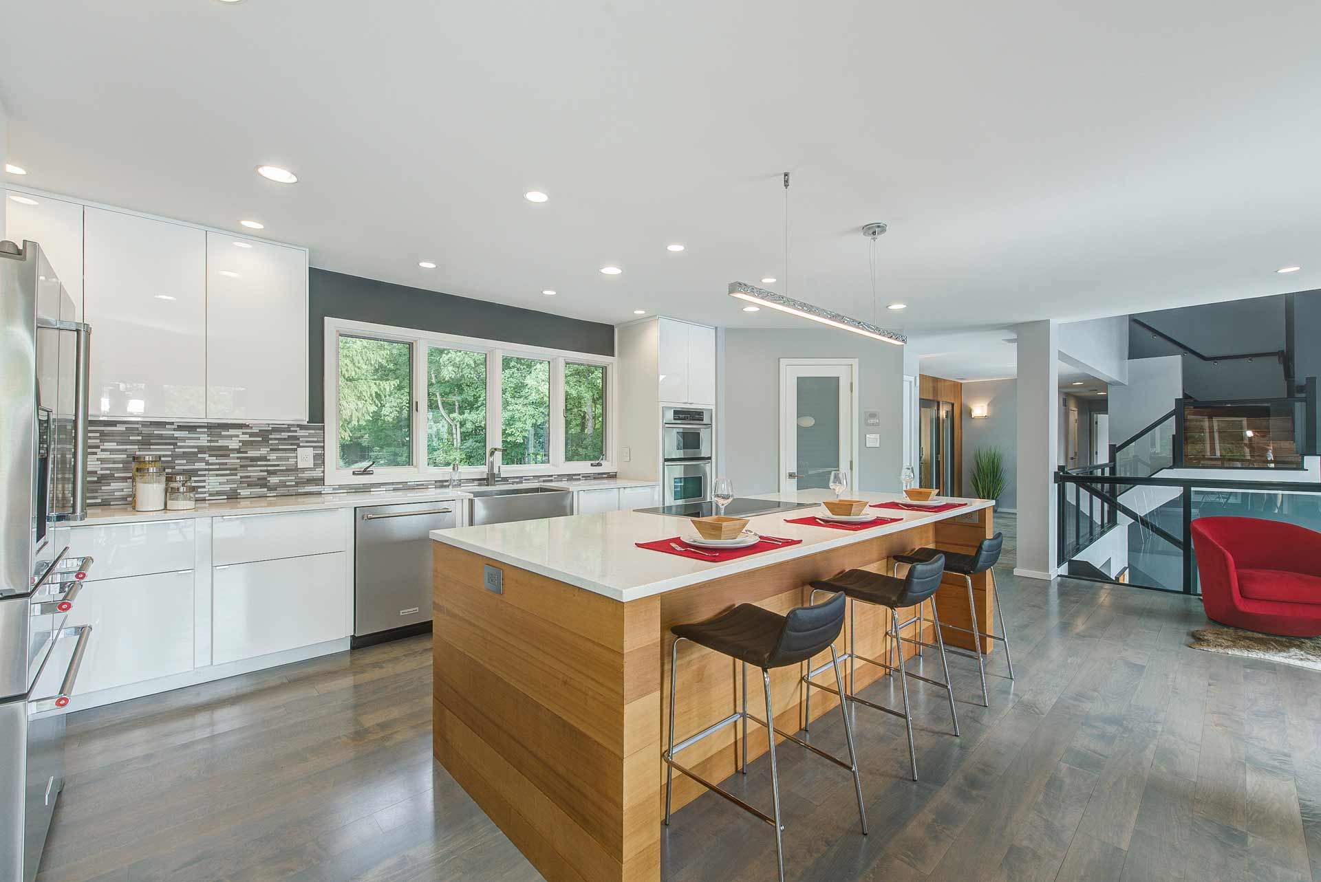 Cedar Wrapped Kitchen Island + White Cabinets and White Quartz Tops - Reef Court Light Renovation - Geist Reservoir - Indianapolis, IN - Red Chair - Photo by Structured Photography