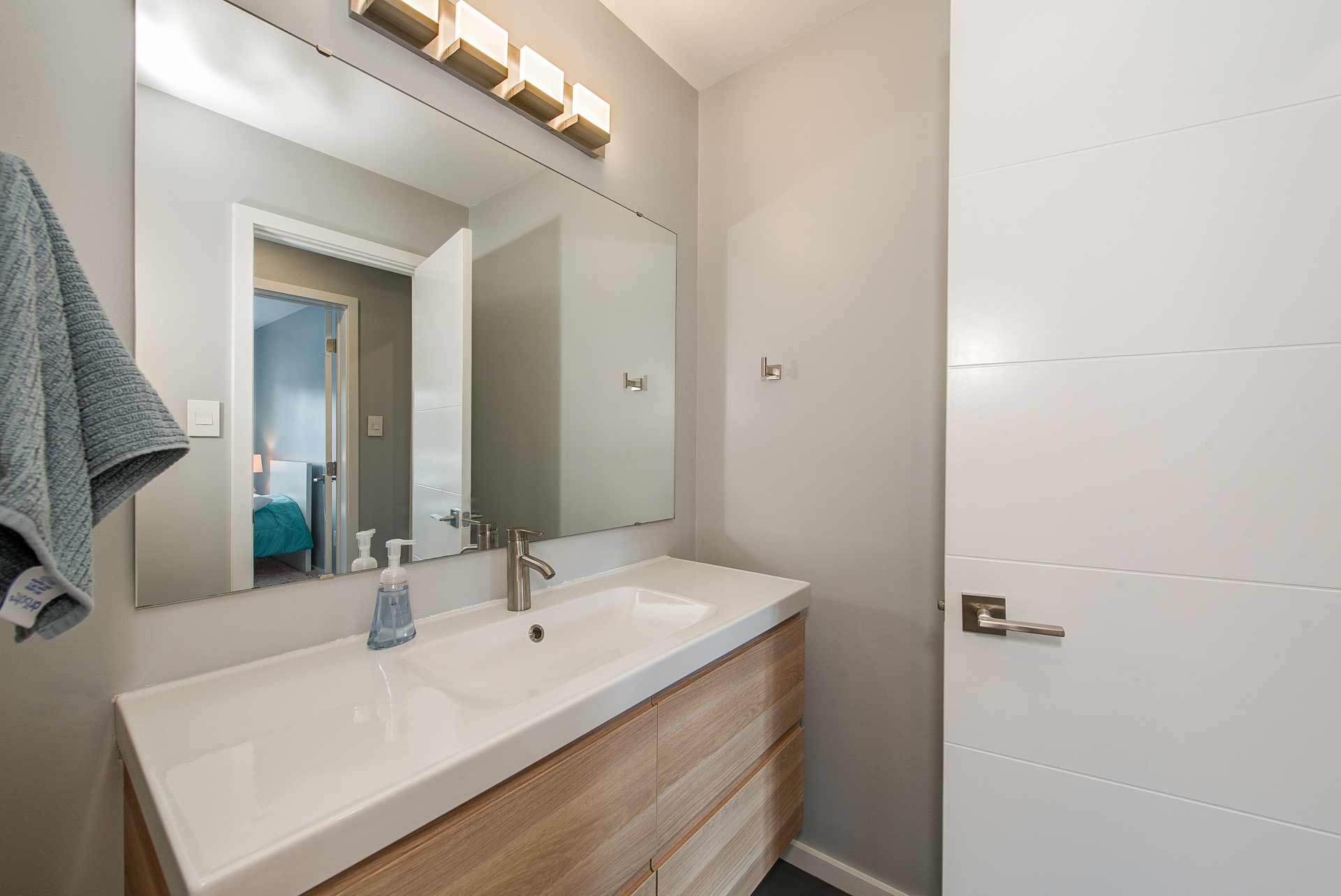 New IKEA wall hung vanity and new door/hardware adorn kid wing bathroom - Reef Court Light Renovation - Geist Reservoir - Indianapolis, IN - Photo by Structured Photography