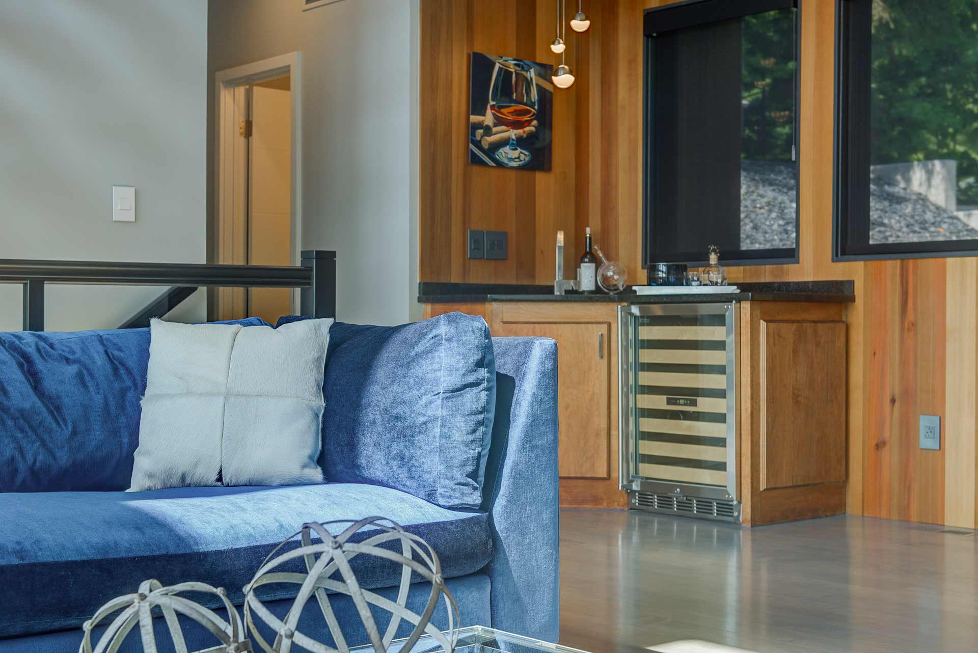 Living space features wet bar (blue sectional sofa) - Reef Court Light Renovation - Geist Reservoir - Indianapolis, IN - Photo by Structured Photography