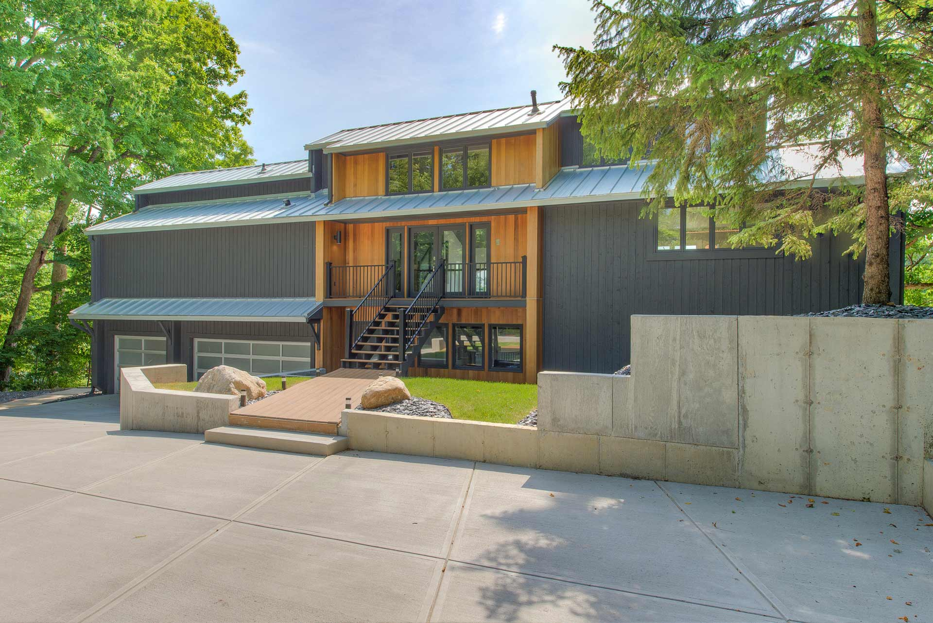 Front exterior elevation has been updated with new modern color, new silver standing seam metal roofs, and Cedar-lined entry core - Reef Court Light Renovation - Geist Reservoir - Indianapolis, IN - Photo by Structured Photography