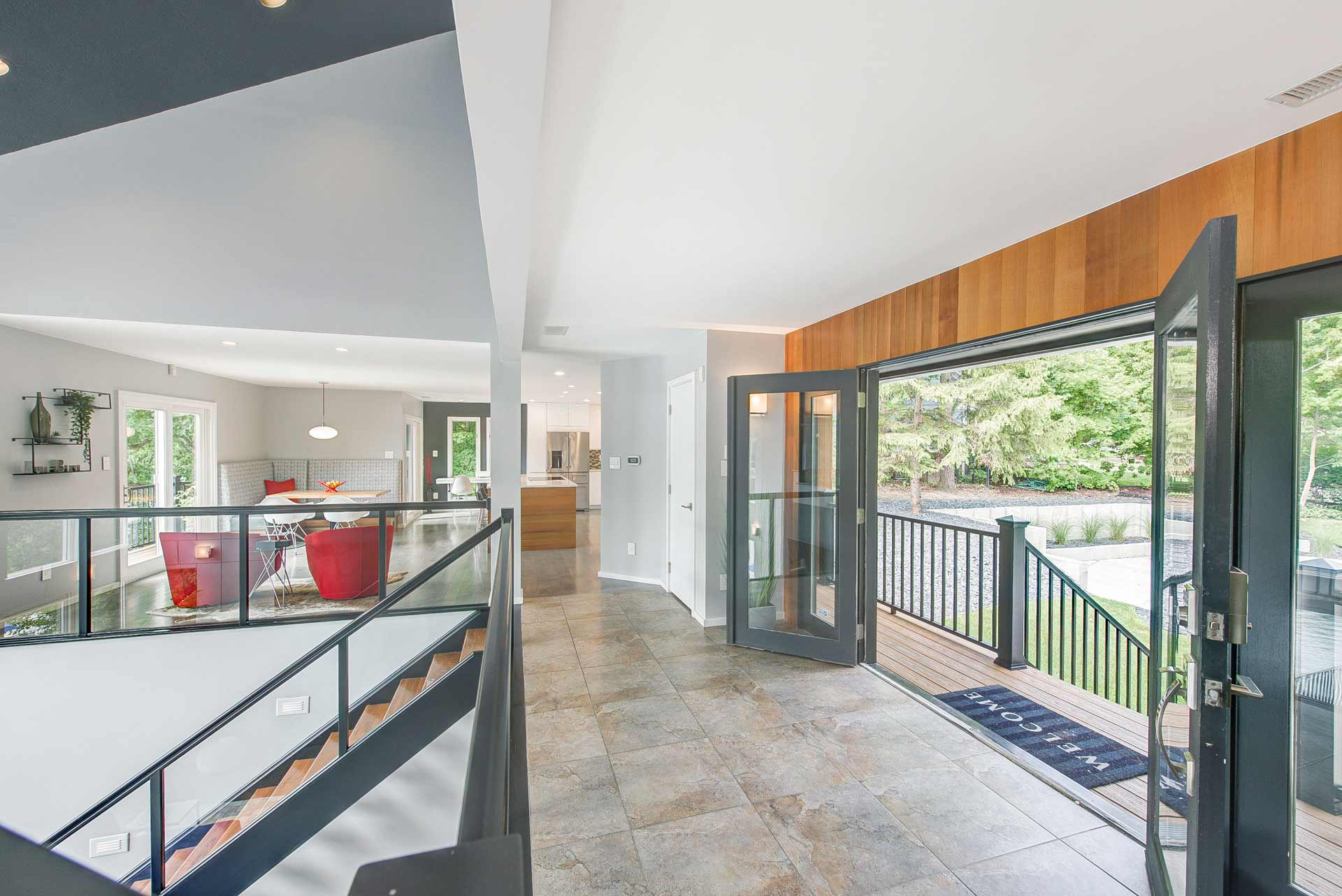Enhanced main entry overlooks vaulted living space below and expanded kitchen + dining space beyond - Reef Court Light Renovation - Geist Reservoir - Indianapolis, IN - Photo by Structured Photography